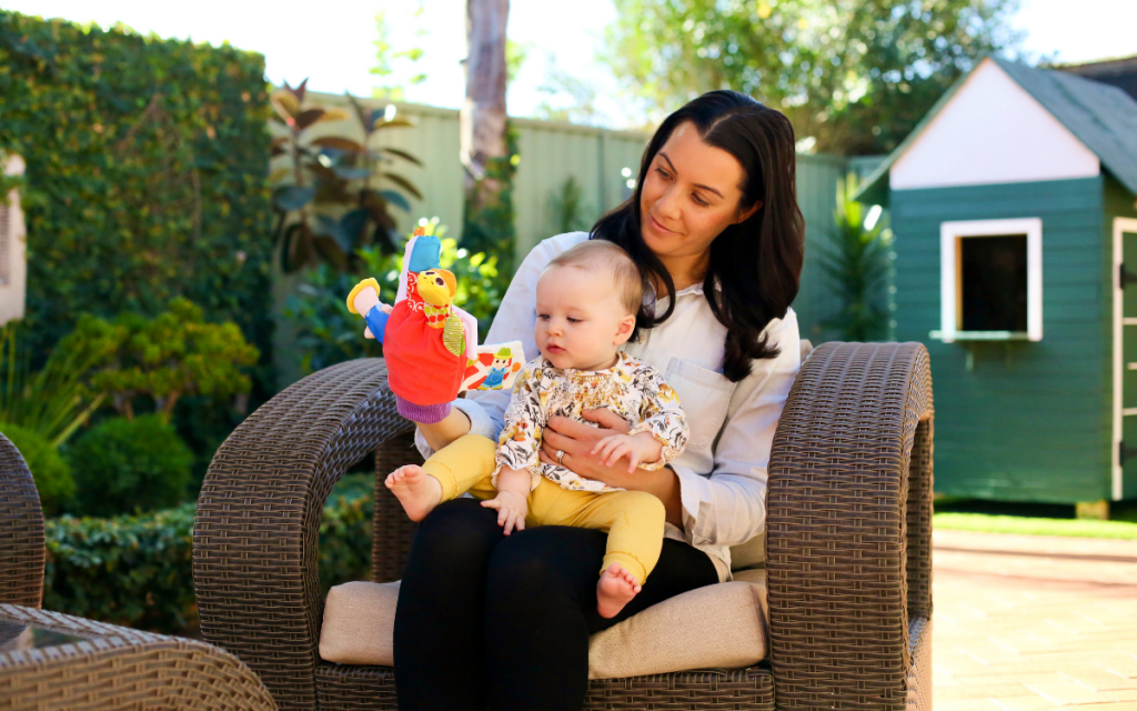 Mother sitting in a backyard with her baby holding a baby toy